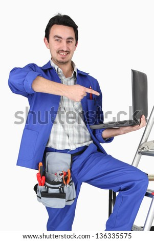 Plumber with a laptop and various tools of the trade - stock photo