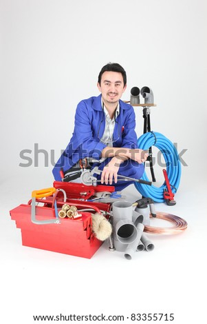 Plumber with a variety of tools and material - stock photo