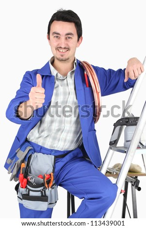 plumber with all his equipment making a thumbs up sign - stock photo