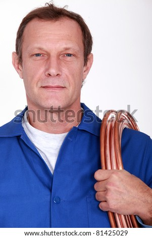 Plumber with coiled copper pipe over shoulder - stock photo