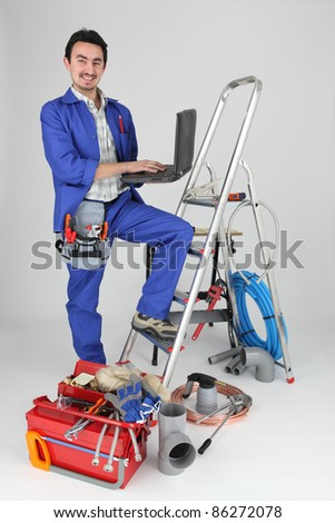 plumber with computer on stepladder - stock photo