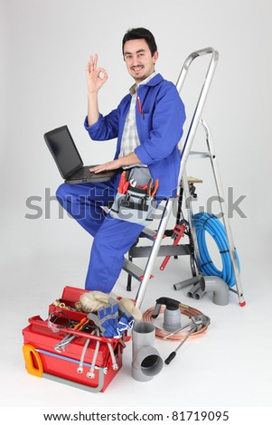 Plumber with laptop and tools on white background - stock photo