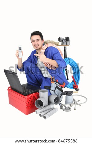 Plumber with laptop, cellphone and materials - stock photo