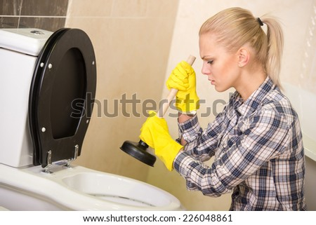 Plumber with rubber plunger in a bathroom. - stock photo