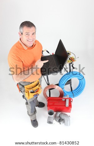 Plumber with tools and a laptop computer with a blank screen - stock photo