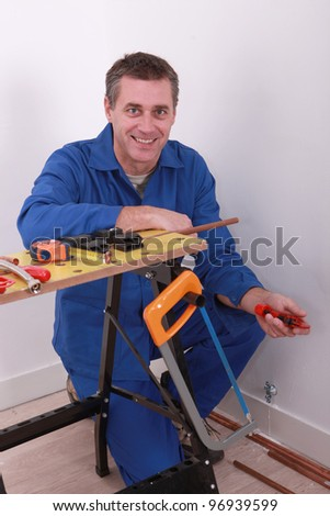Plumber with tools and copper piping - stock photo