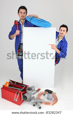 plumber with tools pointing at board - stock photo