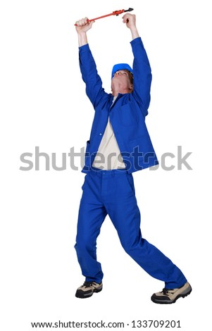 Plumber with wrench reaching into the air - stock photo