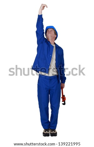 Plumber with wrench reaching upwards - stock photo