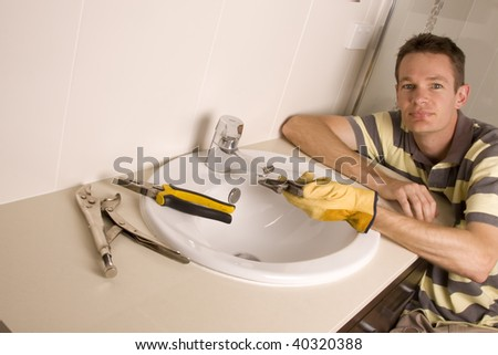 Plumber working on a broken tap in a bathroom sink - stock photo
