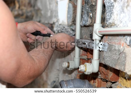 Plumber working on pipes.