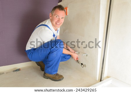 Plumber working with water intallation in bathroom - stock photo