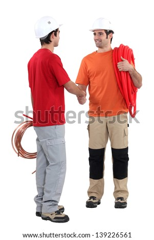 Plumbers shaking hands - stock photo