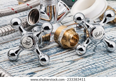 plumbing and accessories on wooden table - stock photo