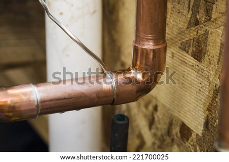 Plumbing contractor works sweating the joints on the copper pipe domestic water system on a luxury custom home - stock photo