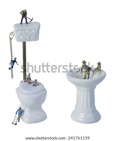 Plumbing Issues shown by workers working on a toilet and sink - stock photo