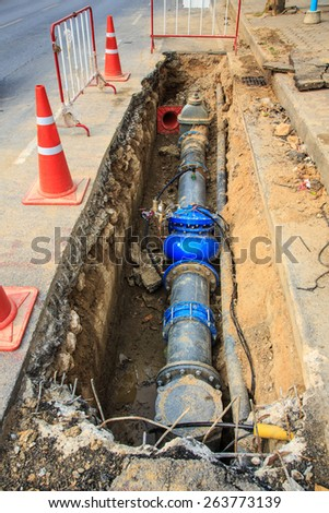 Plumbing repair near footpath in the city. - stock photo