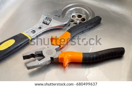 Plumbing Tools Adjustable Wrench And Pliers In A Wet Sink, Closeup