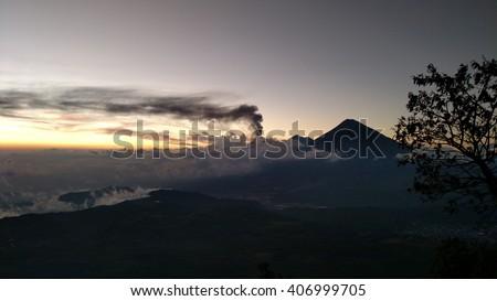 Plume of smoke erupting from Agua Volcano at sunset and trailing across the horizon. Taken from Pacaya Volcano near Antigua, Guatemala - stock photo