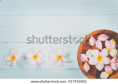 Plumeria flower in a bowl of water on wooden background.