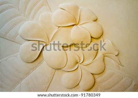 Plumeria flower on a cement wall colors. - stock photo