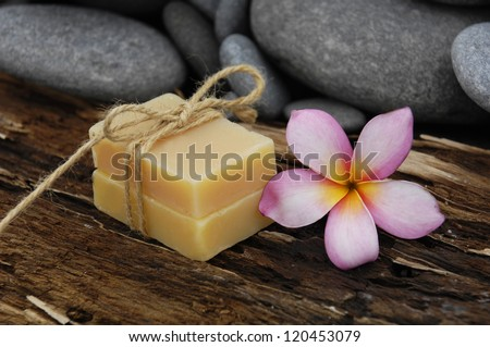 Plumeria with stones and handmade soap on rustic wood texture - stock photo