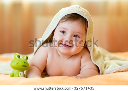 Plump baby girl lying under a hooded towel with after bath - stock photo
