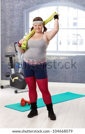 Plump woman at the gym in sportswear, smiling. - stock photo