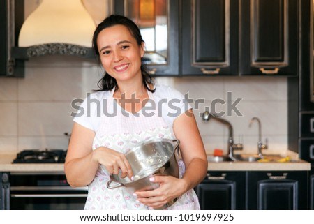 Plump woman cooking on the kitchen. Mature woman in pastel apron kneads a dough in a metal bowl and smiling.