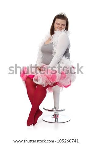 Plump woman posing in tiara and pink tutu, sitting on chair. - stock photo