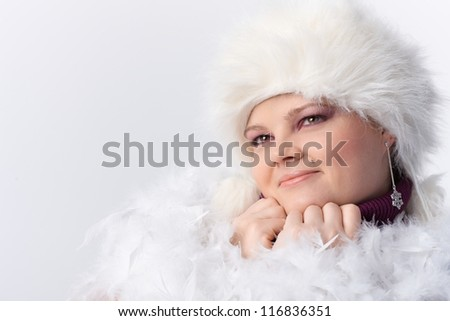 Plump woman smiling among white feathers and fur hat. - stock photo