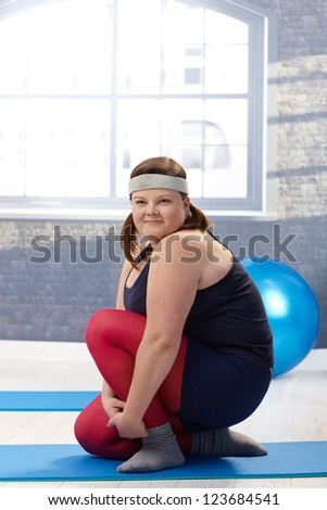 Plump young woman exercising at the gym. - stock photo
