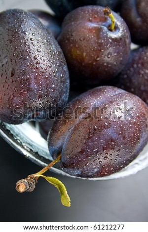 Plums. Fresh ripe washed plums in a glass bowl close-up. - stock photo