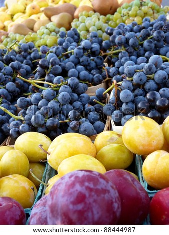 Plums, grapes and pears at a farmers' market.