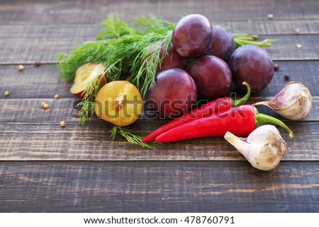 Plums, hot red pepper, garlic, coriander and fennel on rustic wood background. Ingredients for preparation of sauce