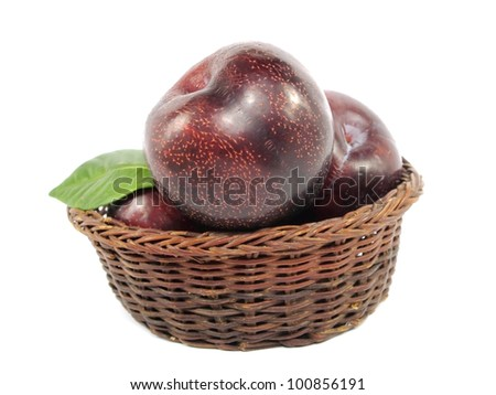 plums in basket on a white background