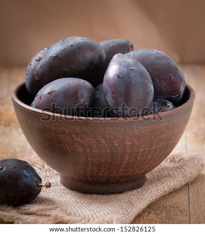 Plums in bowl on wooden table - stock photo