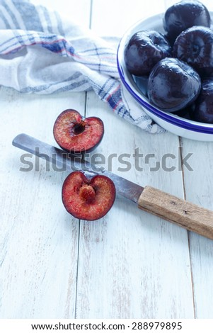 Plums Sliced plums and whole plums on a white rustic background - stock photo
