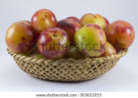 Plums wickerwork oval shape on the white background