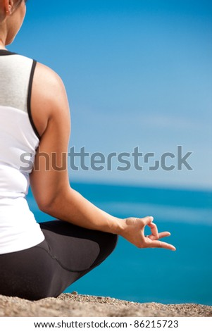 Plus size female practice yoga outdoor under blue sky - stock photo