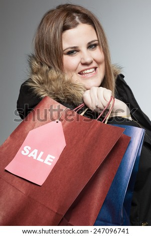 Plus size woman holding shopping bags with sale label.