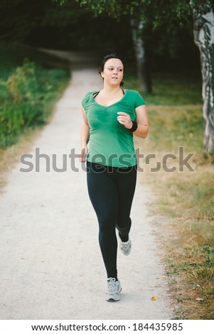 Plus size woman running in park forrest - stock photo