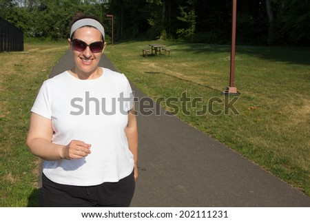 Plus size woman white woman in her 40s walking on a path on a sunny day with sunglasses and a headband in summer - stock photo