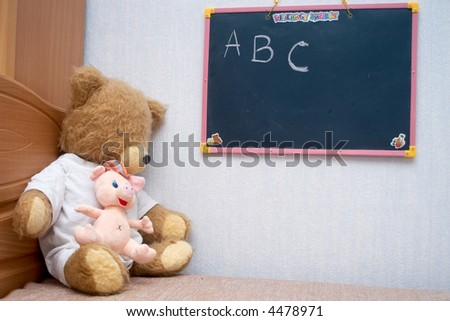 Plush bear sitting at the blackboard