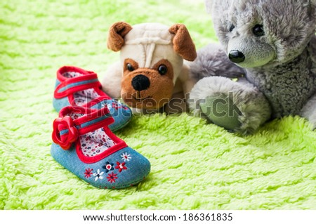 Plush puppy and teddy bear looking at baby shoes. - stock photo