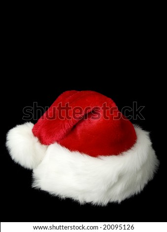 Plush red and white Santa's hat on black background - stock photo
