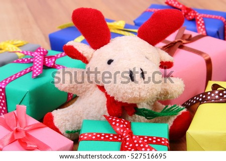 Plush reindeer and heap of wrapped colorful gifts for Christmas, birthday, valentines or other celebration
