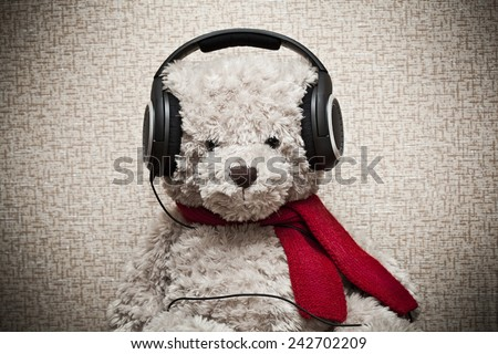 Plush teddy bear listening to music on headphones - stock photo