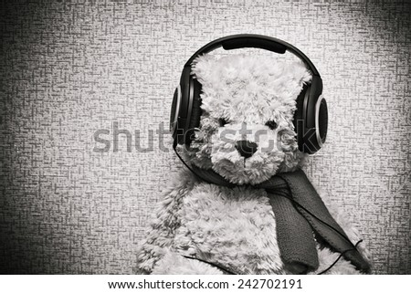 Plush teddy bear listening to music on headphones. Vintage discolored Photo - stock photo