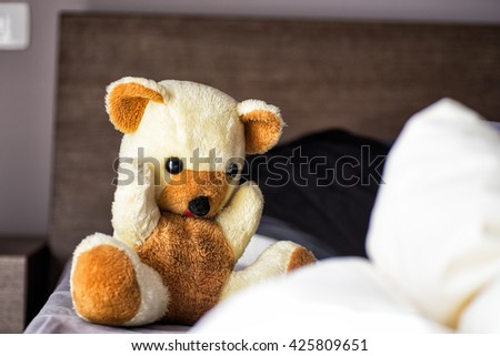 plush teddy bear-shaped sitting on the bed - stock photo